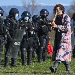 Un activista toca la flauta mientras policías suizos del cantón de Vaud participan en una operación para evacuar la ZAD (Zona de Defensa) de Mormont Hill (Colline du Mormont), cerca de La Sarraz, que está ocupada para protestar contra la ampliación. de la empresa franco-suiza de materiales de construcción LafargeHolcim.   Foto:Fabrice Coffrini / AFP