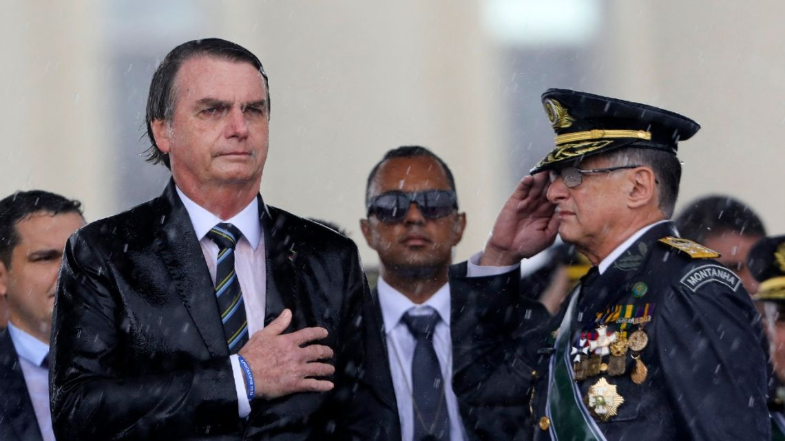 In this file photo taken on April 17, 2019, Brazilian President Jair Bolsonaro (left) and Army Commander Edson Pujol are drenched with rain as they attend a ceremony to mark Army Day, in Brasilia.