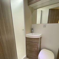 El baño de la unidad está compartimentado: inodoro y bacha por un lado, y ducha de altura completa por otro.