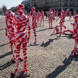 Maniquíes envueltos en cinta de barrera se colocan frente a la histórica Puerta de Brandenburgo de Berlín, como parte del Monumento a la Corona del artista alemán Dennis Josef Meseg llamado  | Foto:John Macdougall / AFP
