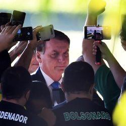 El presidente brasileño, Jair Bolsonaro, habla con sus partidarios cuando abandona el Palacio de la Alvorada en Brasilia. | Foto:Evaristo Sa / AFP