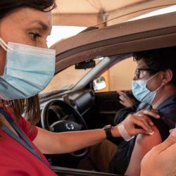 Un trabajador de salud administra una dosis de la vacuna china CoronaVac contra COVID-19 a un hombre en un centro de vacunación en Santiago. | Foto:Martin Bernetti / AFP