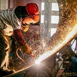 Las chispas vuelan mientras un trabajador produce equipos de ingeniería para la exportación en una fábrica en Nantong, en la provincia de Jiangsu, en el este de China. | Foto:STR / AFP