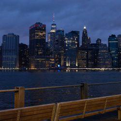 Una persona sentada sola en un banco mirando el horizonte del bajo Manhattan en la ciudad de Nueva York. | Foto:Angela Weiss / AFP