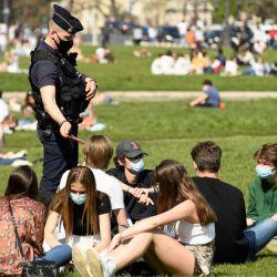 Agentes de policía controlan a personas que disfrutan de un soleado día de primavera en el césped frente al Hotel des Invalides en París, en medio de la pandemia de coronavirus. | Foto:Bertrand Guay / AFP