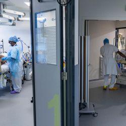 Las enfermeras atienden a un paciente infectado con el Covid-19 acostado en una cama mientras otro paciente infectado con el Covid-19 es transportado por camilleros en una unidad de cuidados intensivos del Hopital Delafontaine en Saint-Denis, suburbio de París. | Foto:Thomas Samson / AFP