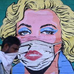 Un peatón pasa junto a un mural de la actriz de Hollywood Marilyn Monroe con una mascarilla para concienciar sobre el coronavirus COVID-19, en Mumbai. | Foto:Indranil Mukherjee / AFP