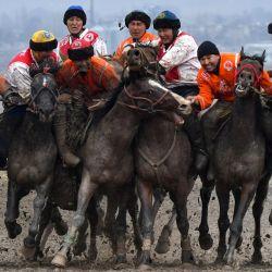Los jinetes kirguisos practican el deporte tradicional de Asia Central de Kok-Boru (lobo gris) en el pueblo de Sokuluk, a unos 20 kilómetros de Bishkek. - Kok-Boru es un juego de caballos tradicional donde los jugadores montados compiten por puntos maniobrando una piel de oveja de peluche en el poste de la portería del oponente. | Foto:Vyacheslav Oseledko / AFP