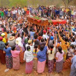 Esta foto tomada y recibida de una fuente anónima a través de Facebook muestra a los dolientes haciendo el saludo de tres dedos durante los funerales conjuntos de tres manifestantes, quienes fueron asesinados a tiros el día anterior en medio de una represión de las fuerzas de seguridad contra las manifestaciones contra el ejército. golpe, en Monywa, región de Sagaing. | Foto:Handout / FACEBOOK / AFP