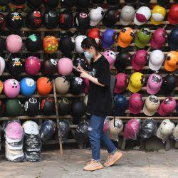 Una mujer pasa junto a un puesto callejero que vende cascos en Hanoi. | Foto:Nhac Nguyen / AFP