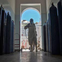 Un hombre yemení que llevaba un equipo de protección desinfecta una sala de hospital que alberga a pacientes con Covid-19 en la tercera ciudad de Taez, en Yemen. | Foto:Ahmad Al-Basha / AFP