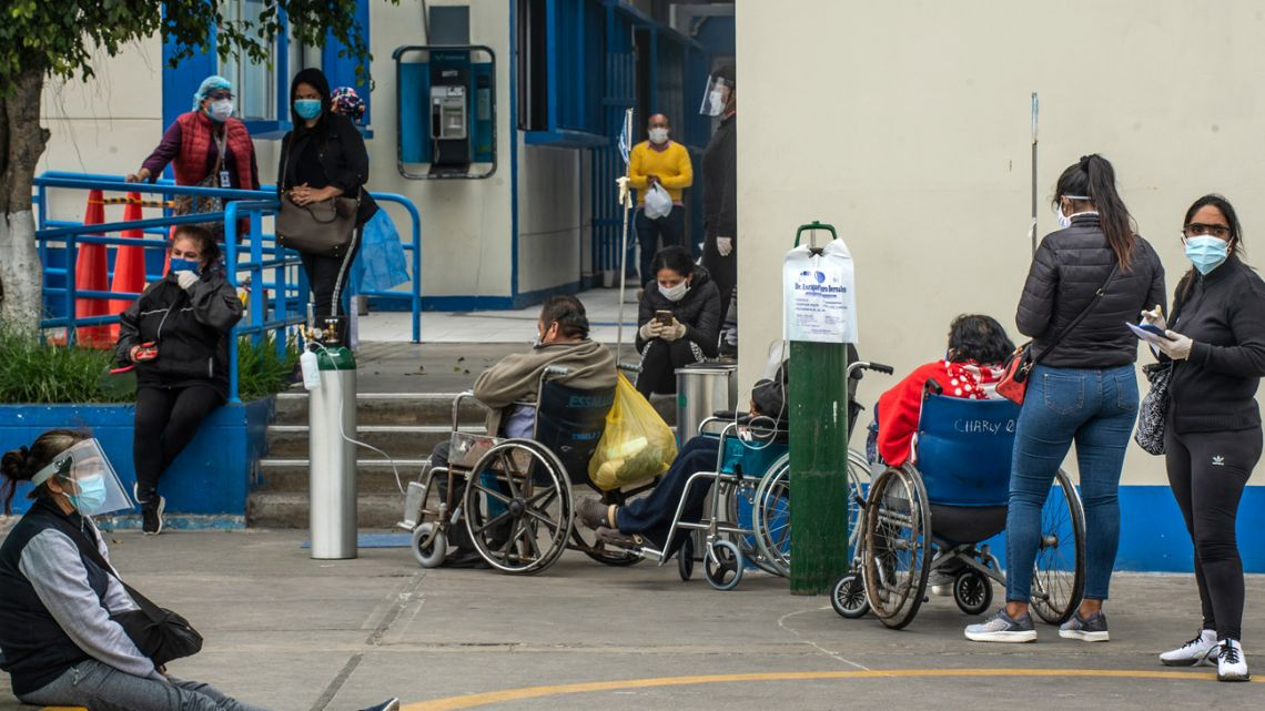 People await to receive medical attention outside the emergency area at Alberto Sabogal Hospital in Lima.