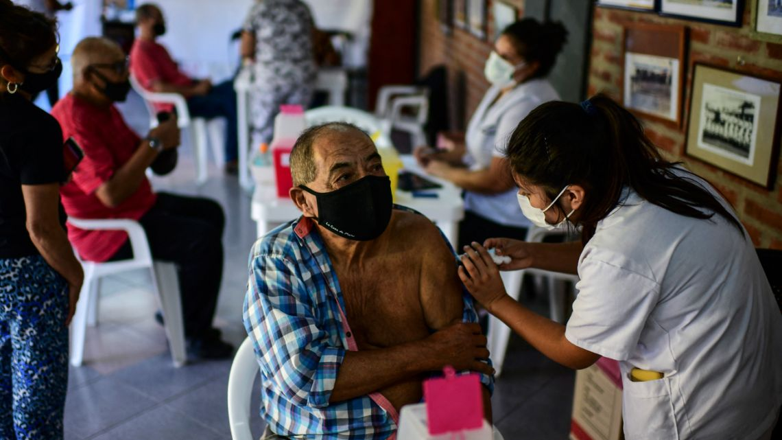 A health worker applies a dose of the Sputnik V vaccine against COVID-19, at the Centenario stadium in Quilmes, Buenos Aires province, on April 1, 2021.