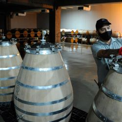 A worker controls barrels at an experimental sector of the Rutini winery in Valle de Uco, Tupungato.