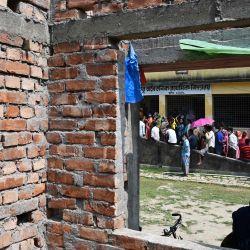 La gente hace cola para emitir su voto en un colegio electoral durante la tercera fase de las elecciones legislativas estatales, en el distrito de South Twenty Four Parganas, a unos 70 km de Calcuta. | Foto:Dibyangshu Sarkar / AFP