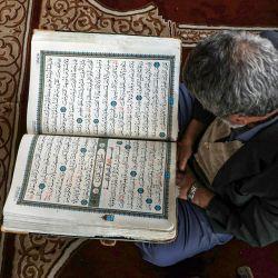 Un hombre lee una versión impresa grande del Corán, el libro sagrado del Islam, en la Gran Mezquita de la capital de Yemen, Sanaa, mientras los creyentes se preparan en la semana previa al mes sagrado de ayuno musulmán del Ramadán. | Foto:Mohammed Huwais / AFP