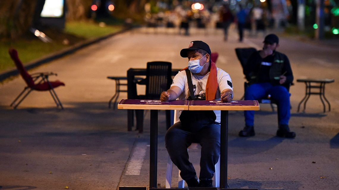 A waiter sits at one of the restaurant tables that block a street during a protest by the sector against the measures taken by the national government to prevent the spread of COVID-19, in Cali, Colombia, on April 5, 2021.