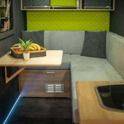 Buena parte del interior está ocupado por un sillón en forma de L y una pequeña mesa plegable.