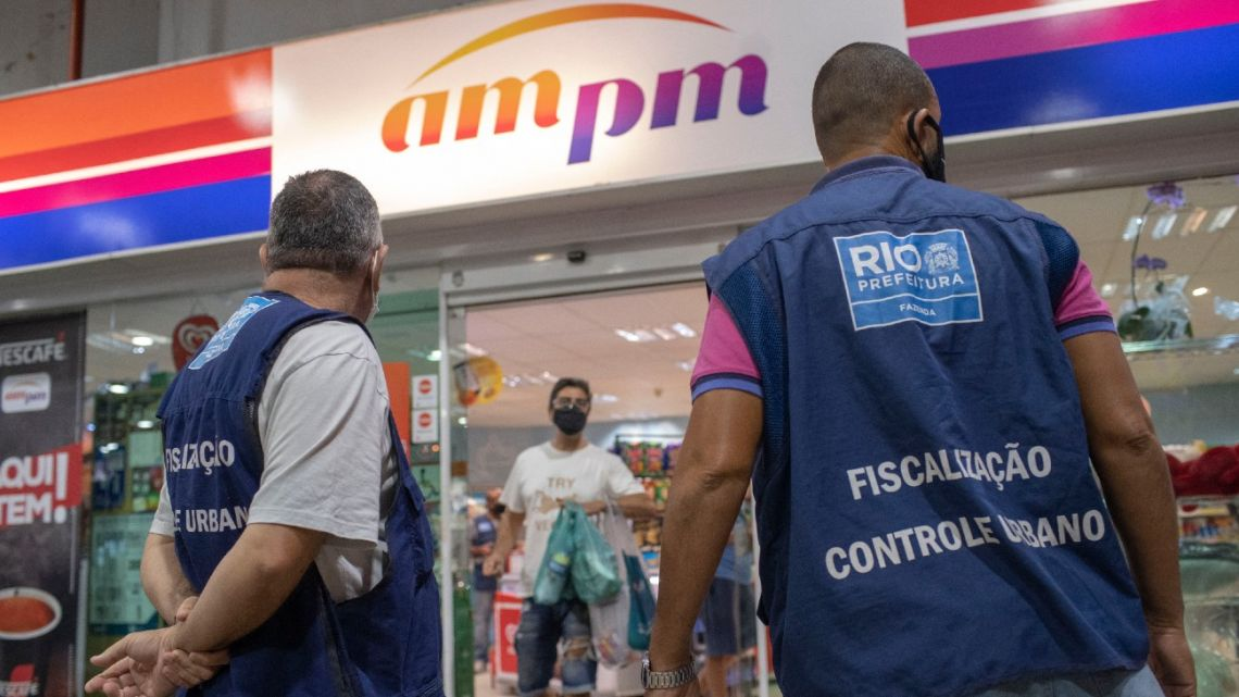In this file photo taken on April 2, 2021, health surveillance agents are seen applying a fine and shutting down for a day a gas station store after not following Covid-19 restrictions imposed by Rio de Janeiro's City Hall during an operation at the Barra da Tijuca neighbourhood, in Rio de Janeiro, Brazil.