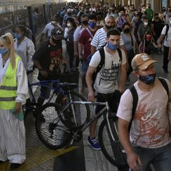 Una trabajadora espera para desinfectar la cabina de un tren de cercanías mientras los pasajeros descienden en la estación de tren Once en Buenos Aires, en medio de la pandemia del nuevo coronavirus. | Foto:AFP