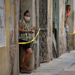 Personas paran en la puerta de sus casas en un área restringida luego de que se detectaran casos de COVID-19 en La Habana. - Las autoridades cubanas anunciaron nuevas medidas para controlar un aumento de COVID-19 con mayores penas para las personas que lo hagan, no cumplir con la normativa sanitaria y las campañas para persuadir a la población de que se tome más en serio el riesgo. | Foto:Yamil Lage / AFP
