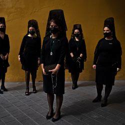 Mujeres vestidas de negro y con la tradicional 'Mantilla' posan en el arco de la Macarena cerca de la Basílica de la Macarena, en Sevilla. | Foto:Cristina Quicler / AFP