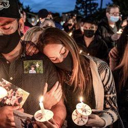 Rafael Farias (izquierda), padre de Matthew de 9 años, llora con Rosie Farias y Mary Alcaraz durante una vigilia con velas y un rosario por las víctimas del tiroteo en Orange fuera de las oficinas de Unified Homes. | Foto:Leonard Ortiz / Registro del Condado de Orange vía ZUMA / DPA