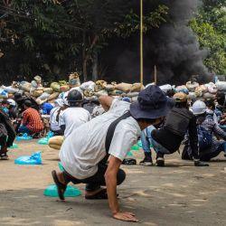 Esta foto tomada y recibida de una fuente anónima a través de Facebook muestra a los manifestantes refugiándose detrás de barricadas improvisadas durante una manifestación contra el golpe militar en el municipio de Thaketa en Yangon. | Foto:Handout / FACEBOOK / AFP