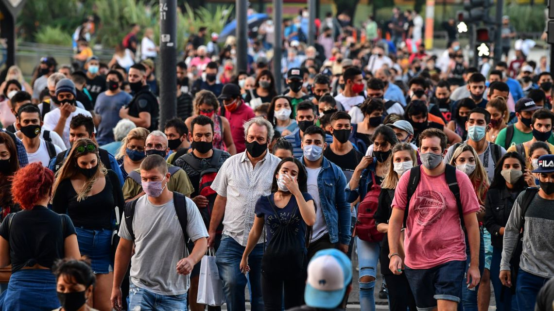 People wearing protective face masks walk by Avenida Brasil, near the Constitución train station in Buenos Aires City, on April 6, 2021.