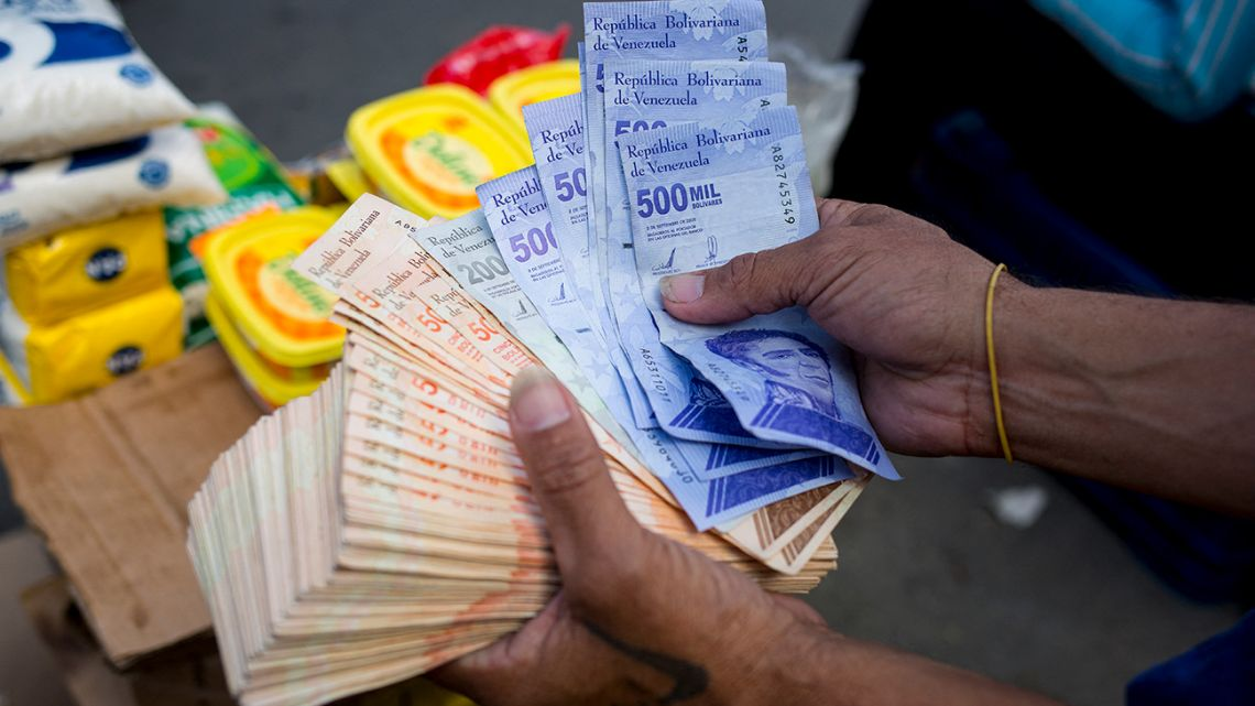 A man holds Bolivar bills a street market in Caracas' Catia neighbourhood, on April 6, 2021, amid the Covid-19 pandemic.