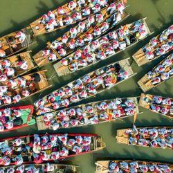 Esta foto aérea muestra a los barcos que se preparan para participar en una actuación durante el festival de barcos de Qintong en Taizhou, en la provincia oriental de Jiangsu, en China. | Foto:STR / AFP