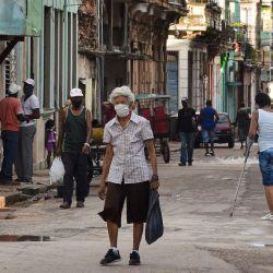 Un anciano con mascarilla camina por una calle de La Habana. - En medio de largas colas por comida y los efectos de la pandemia, los cubanos ven sin muchas esperanzas el cambio de batuta entre Raúl Castro y Miguel Díaz-Canel. como primer secretario del Partido Comunista de Cuba, el cargo más alto del país. | Foto:Yamil Lage / AFP