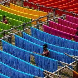 India, Shantipur: los trabajadores cuelgan hilos de tela para que se sequen después de teñirlos en una fábrica de teñido. | Foto:Saurabh Sirohiya / ZUMA Wire / DPA