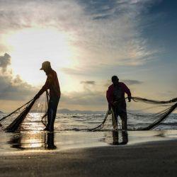 Los pescadores limpian sus redes después de pescar durante la puesta de sol en una playa en Banda Aceh.   Foto:Chaideer Mahyuddin / AFP