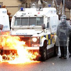 Las llamas se ven en la parte delantera de un vehículo policial cuando los policías son atacados por jóvenes nacionalistas en el área de Springfield Road en Belfast, luego de días de violencia. | Foto:Paul Faith / AFP