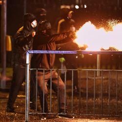 Los manifestantes disparan fuegos artificiales contra la policía antidisturbios en la carretera de Springfield, mientras sindicalistas y nacionalistas se enfrentaban con la policía y entre ellos. | Foto:Liam Mcburney / PA Wire / DPA