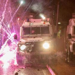 Los fuegos artificiales explotaron en vehículos policiales después de ser disparados contra oficiales de policía durante enfrentamientos con jóvenes nacionalistas en el área de Springfield Road en Belfast mientras el desorden continuaba en la capital de Irlanda del Norte luego de días de violencia.   Foto:Paul Faith / AFP