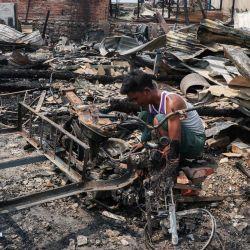Un residente recupera artículos después de un incendio durante la noche que envolvió más de 100 casas en Mandalay, mientras el país continúa en crisis después del golpe militar de febrero.   Foto:STR / AFP