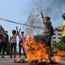 Los manifestantes hacen el saludo de tres dedos mientras se queman copias de la constitución de 2008 durante una manifestación contra el golpe militar en el municipio de Okkalapa del sur de Yangon. | Foto:STR / AFP