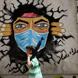 Un niño palestino camina con una pistola de juguete junto a un mural de COVID-19 en el campo de refugiados de al-Fawwar al suroeste de Hebrón en la ocupada Cisjordania. | Foto:Hazem Bader / AFP