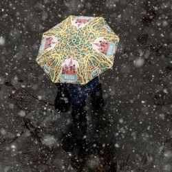 Una mujer camina bajo un paraguas con la imagen de la Catedral de San Basilio durante una nevada en Moscú.   Foto:Kirill Kudryavtsev / AFP