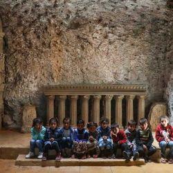 Los niños se sientan junto a una réplica en miniatura de una columnata dórica mientras son sermoneados por Abd al-Aati Said (no visible en la foto), un arquitecto desplazado de 54 años de la campiña de Alepo que huyó del conflicto, en su recién creado museo cueva de Siria. patrimonio y cultura cerca de la ciudad de Aqrabat en el campo de la provincia de Idlib, noroeste de Siria. | Foto:Aaref Watad / AFP)