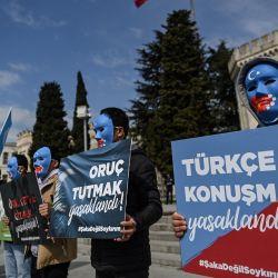 Manifestantes con una máscara pintada con los colores de la bandera de Turkestán Oriental sostienen carteles que dicen  | Foto:Ozan Kose / AFP