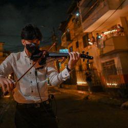 Un hombre toca el violín durante un homenaje en honor a las 4008 muertes registradas por Coronavirus, en Medellín, Colombia.   Foto:Joaquin Sarmiento / AFP