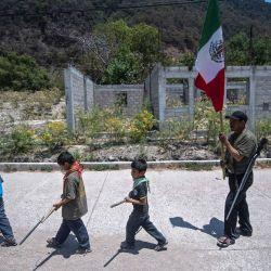 Niños caminan por una calle mientras se preparan para participar en una manifestación de capacitación de la fuerza de vigilancia de la Coordinadora Regional de Autoridades Comunitarias (CRAC-PF), en la vereda Ayahualtempa, Estado de Guerrero, México. - La CRAC -Grupo de vigilantes de la FP entrena a niños de hasta cinco años para que puedan protegerse de los grupos delictivos relacionados con las drogas que operan en la zona.   Foto:Pedro Pardo / AFP