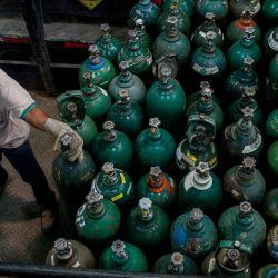 Un empleado prepara cilindros de oxígeno para ser utilizados por pacientes con COVID-19 en Caracas. - Al igual que el resto de América del Sur, Venezuela está luchando contra una nueva y dura ola pandémica alimentada, dicen las autoridades, por más variantes de virus infecciosos de Brasil. | Foto:Pedro Rances Mattey / AFP