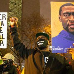 Un manifestante sostiene un retrato de George Floyd mientras levanta el puño durante una marcha contra la brutalidad policial en medio del juicio de Derek Chauvin en el centro de Minneapolis. | Foto:Henry Pan / Zuma Wire / DPA