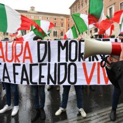 Los manifestantes que ondean las banderas nacionales de Italia sostienen una pancarta que dice  | Foto:Alberto Pizzoli / AFP