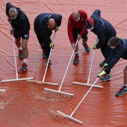 Los miembros del personal de tierra barren el agua de las cubiertas de la cancha ya que el juego se suspende debido a la lluvia en el segundo día del torneo de tenis Monte-Carlo ATP 1000 Masters Series en Montecarlo, Mónaco. | Foto:Valery Hache / AFP