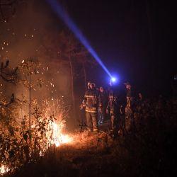 Los bomberos están trabajando para extinguir un incendio forestal en el área de Nagarkot del distrito de Bhaktapur, a unos 32 km al norte, al este de Katmandú. | Foto:Prakash Mathema / AFP